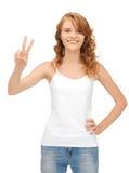 Muchacha en la camiseta blanca en blanco que muestra la muestra de la victoria Imágenes de archivo libres de regalías