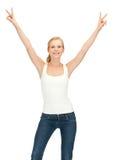 Muchacha en la camiseta blanca en blanco que muestra la muestra de la victoria Foto de archivo