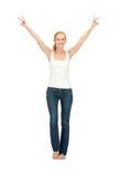 Muchacha en la camiseta blanca en blanco que muestra la muestra de la victoria Imagen de archivo libre de regalías