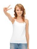 Muchacha en la camiseta blanca en blanco que muestra la muestra de la victoria Fotografía de archivo