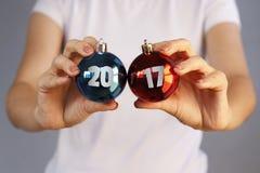 Muchacha en la camiseta blanca que sostiene la bola del juguete dos de la Navidad Rojo, azul Imagen de archivo libre de regalías