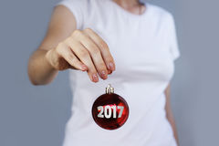 Muchacha en la camiseta blanca que sostiene la bola roja del juguete de la Navidad con inscri Fotos de archivo