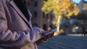 Muchacha en la capa que congela en la calle, llamando el taxi, usando el app en línea de los gps para encontrar el café metrajes