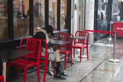 Muchacha en la capa y el sombrero que se sientan en una tabla roja en un café al aire libre en la lluvia imágenes de archivo libres de regalías