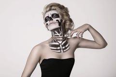 Muchacha en la cara del esqueleto Fotos de archivo