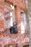 Muchacha en la casa arruinada del ladrillo Imagenes de archivo