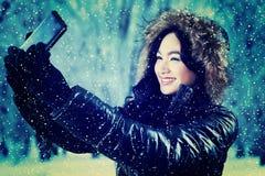 Muchacha en la chaqueta del invierno que toma el autorretrato Foto de archivo
