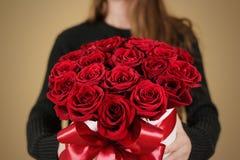 Muchacha en la chaqueta negra que sostiene el ramo rico disponible del regalo del rojo 21 Imagenes de archivo