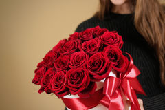 Muchacha en la chaqueta negra que sostiene el ramo rico disponible del regalo del rojo 21 Imagen de archivo libre de regalías