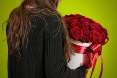 Muchacha en la chaqueta negra que sostiene el ramo rico disponible del regalo del rojo 21 Imágenes de archivo libres de regalías