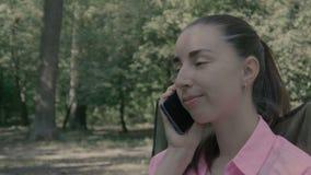 Muchacha en la charla del bosque sobre el teléfono metrajes