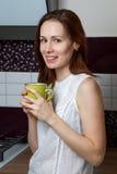 Muchacha en la cocina con una taza Imagen de archivo