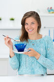 Muchacha en la cocina que come el desayuno Foto de archivo