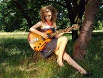 Muchacha en la comida campestre con la guitarra Imagen de archivo