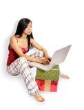 Muchacha en la computadora portátil con los regalos Imágenes de archivo libres de regalías