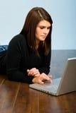 Muchacha en la computadora portátil en suelo Imagen de archivo