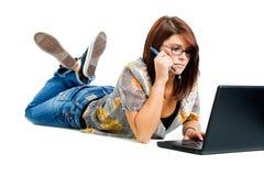 Muchacha en la computadora portátil que sostiene una pluma Foto de archivo libre de regalías