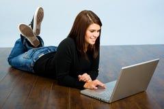 Muchacha en la computadora portátil en suelo Fotos de archivo libres de regalías