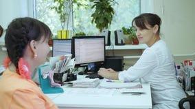 Muchacha en la consulta del ` s del doctor Un doctor de sexo femenino hace una tarjeta paciente electrónica almacen de metraje de vídeo