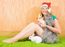 Muchacha en la decoración del Año Nuevo con los conejos Foto de archivo libre de regalías