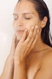 Muchacha en la ducha que se lava la cara Foto de archivo