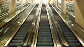 Muchacha en la escalera móvil Imágenes de archivo libres de regalías