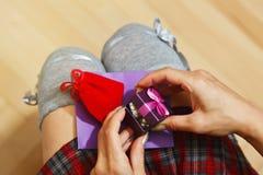 Muchacha en la falda de la colegiala que abre una caja de regalo Fotografía de archivo libre de regalías