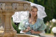 Muchacha en la fuente con el paraguas blanco Imagenes de archivo