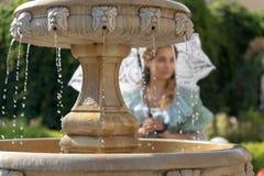 Muchacha en la fuente con el paraguas blanco Fotografía de archivo libre de regalías