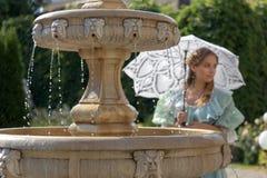 Muchacha en la fuente con el paraguas blanco Foto de archivo libre de regalías