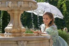 Muchacha en la fuente con el paraguas blanco Foto de archivo