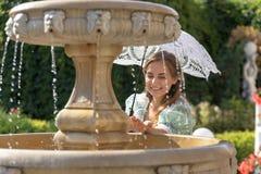 Muchacha en la fuente con el paraguas blanco Imagen de archivo