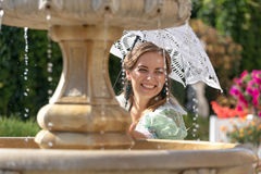 Muchacha en la fuente con el paraguas blanco Fotos de archivo libres de regalías