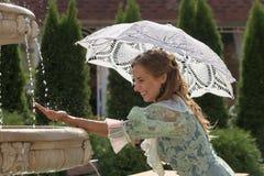 Muchacha en la fuente con el paraguas blanco Imágenes de archivo libres de regalías