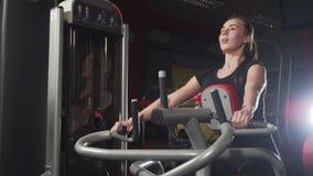 Muchacha en la gimnasia Entrenamiento del peso Trabajo sobre los músculos de la parte posterior Mujeres que se resuelven en el ap almacen de metraje de vídeo