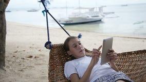 Muchacha en la hamaca con la tableta en la playa almacen de metraje de vídeo