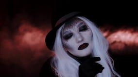 Muchacha en la imagen de un sombrero de la bruja Fondo negro almacen de video