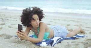 Muchacha en la línea de la playa arenosa que toma el selfie metrajes