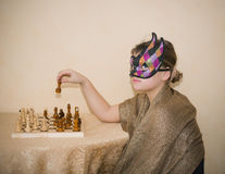 Muchacha en la máscara de teatro que se sienta detrás de la tabla y que juega a ajedrez Foto de archivo