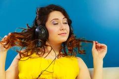 Muchacha en la música que escucha mp3 de los auriculares grandes que se relaja Imágenes de archivo libres de regalías