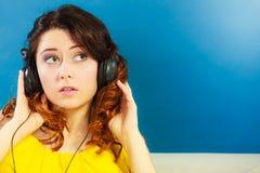 Muchacha en la música que escucha mp3 de los auriculares grandes que se relaja Imagenes de archivo