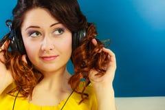 Muchacha en la música que escucha mp3 de los auriculares grandes que se relaja Fotografía de archivo