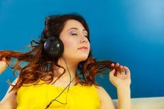 Muchacha en la música que escucha mp3 de los auriculares grandes que se relaja Foto de archivo libre de regalías