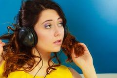 Muchacha en la música que escucha mp3 de los auriculares grandes que se relaja Fotos de archivo