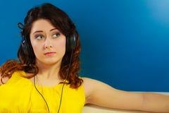 Muchacha en la música que escucha mp3 de los auriculares grandes que se relaja Foto de archivo