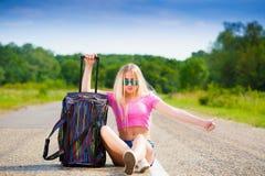 Muchacha en la maleta del camino, camiseta rosada, pantalones cortos azules, altura completa Imagen de archivo libre de regalías