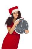 Muchacha en la Navidad con un reloj con las doce Fotografía de archivo
