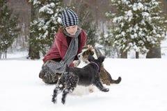 Muchacha en la nieve con sus perros Imagen de archivo