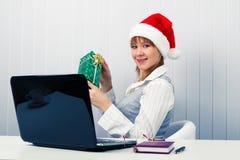 Muchacha en la oficina en los sombreros de Papá Noel con un ordenador portátil y un regalo Fotos de archivo libres de regalías
