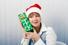 Muchacha en la oficina en los sombreros de Papá Noel con un regalo Imagen de archivo